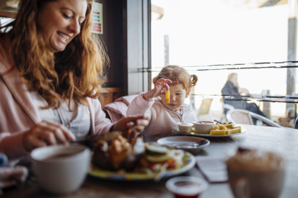 Young family enjoying food at a cafe. The mother is enjoying her food. The little girl is looking at a chip she is holding